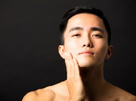 Beautiful Chinese man's face on dark background